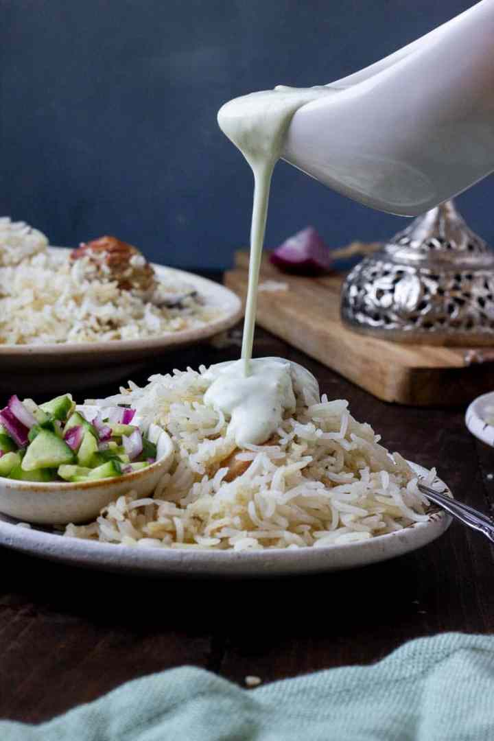a plate of white biryani with raita being poured over top