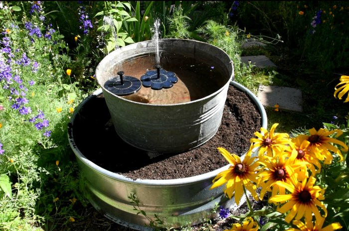 galvanized tub with solar fountains on top of a soil filled fire ring planter