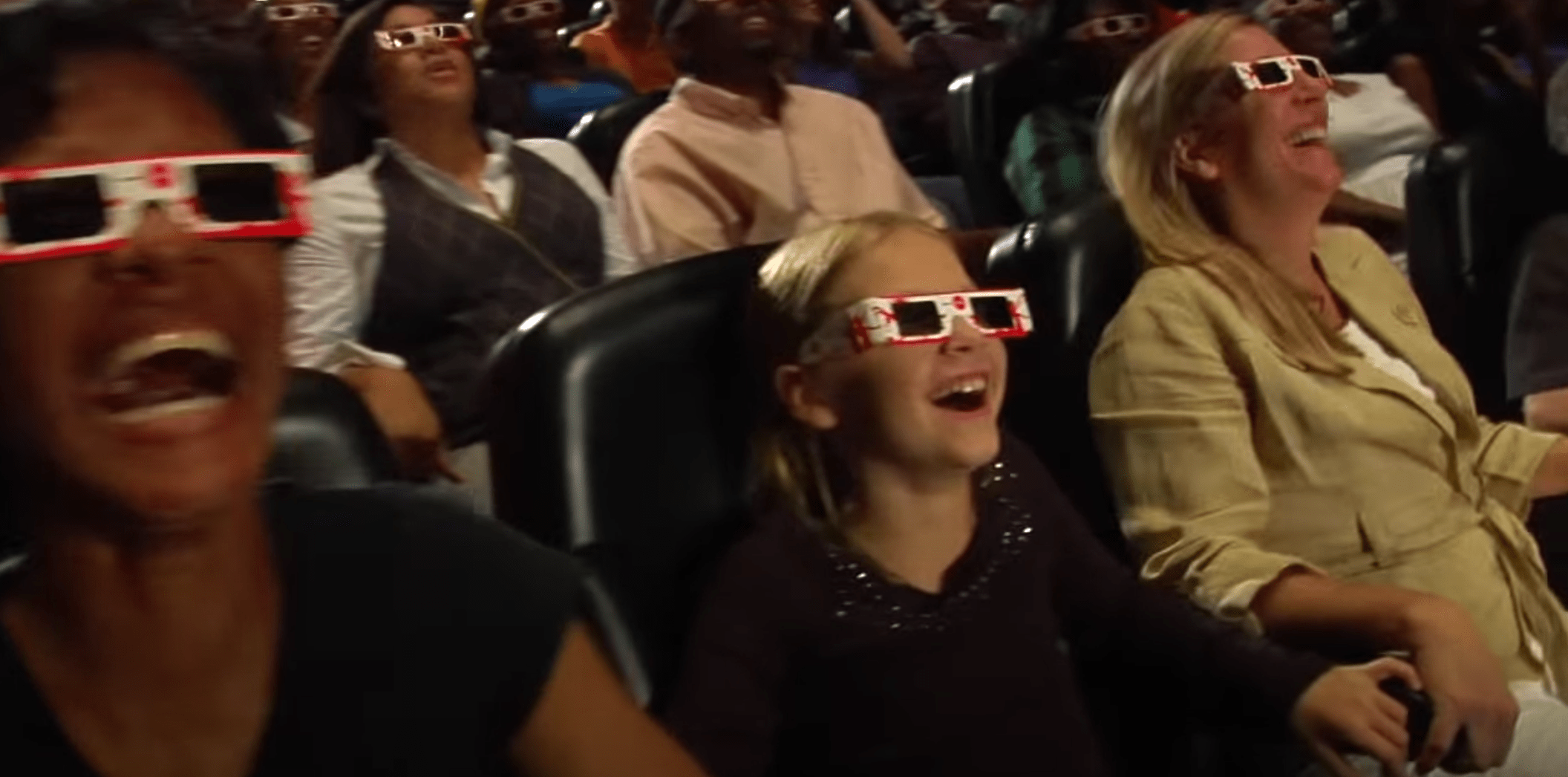 Audience members at the World of Coca-Cola wear 3-D glasses while watching a video.