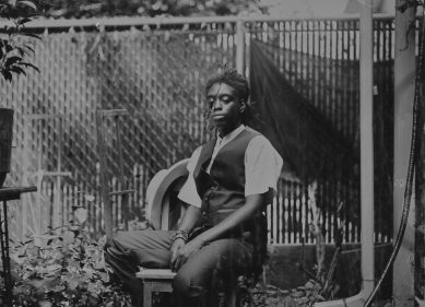 Black and white photo of a young person wearing a black suit vest, white short sleeve shirt and black dress pants sits on a chair in a backyard.
