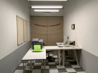"""A small space set up with an L-shaped desk that holds a computer monitor, a printer with green paper, and stationary. The floor is grey and white checkered tile. The beige double doors behind the desk has a banner that says, """"EVERYTHING IS TEMPORARY""""."""
