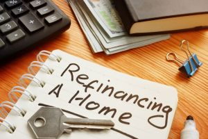 """a notepad with """"refinancing a home"""" written on the page"""