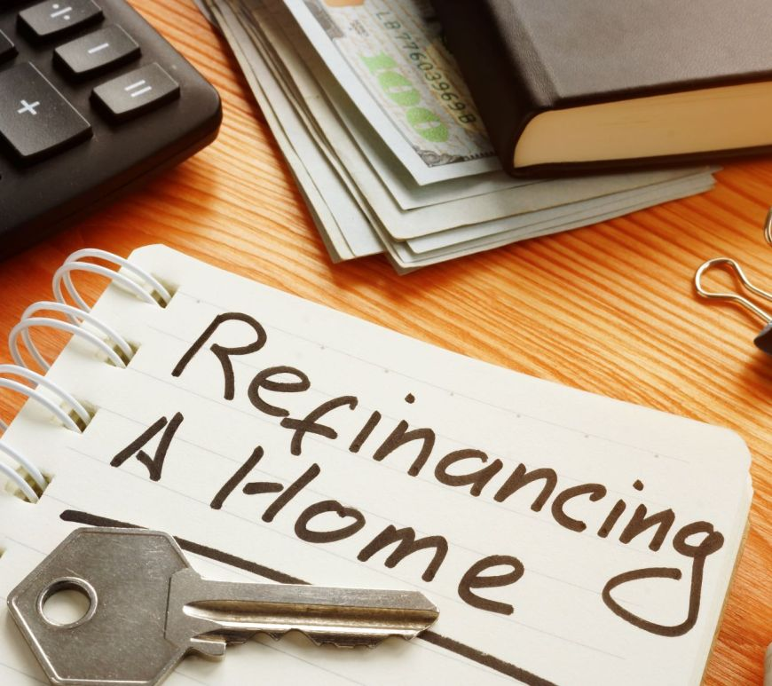 "a notepad with ""refinancing a home"" written on the page"