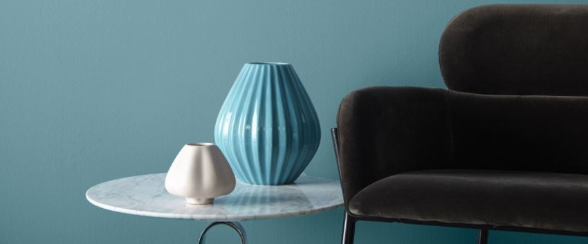 A tranquil blue wall with a gray chair and vases