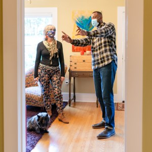 real estate agent and woman touring house, wearing masks