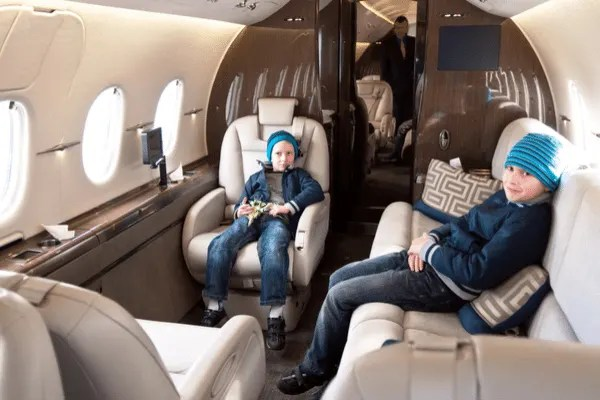 Two young boys sitting on a private jet.
