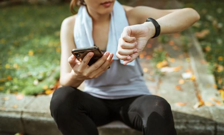 Una donna fa il pairing tra smartphone e smartband durante una sessione di jogging