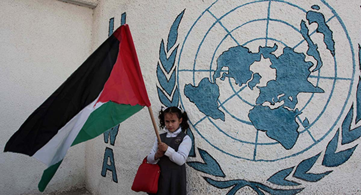 NEWSpalestinian-girl-with-flag-in-front-on-unrwa-logo