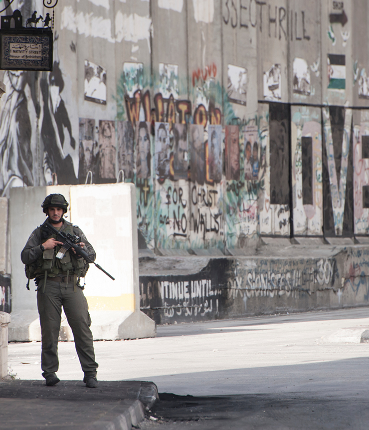 Israeli soldier seen standing near the aparthied wall
