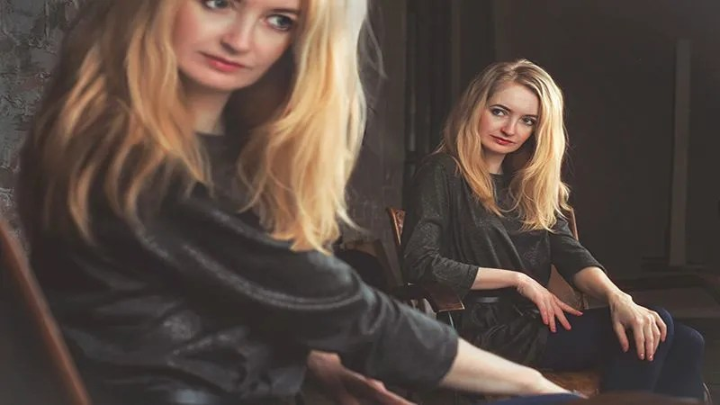 Blonde vrouw kijkt in de spiegel