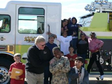 Jan Christensen with the students from Earl Hanson Elementary School after completion of the fire safety training at the Fol-Da-Tank Company.