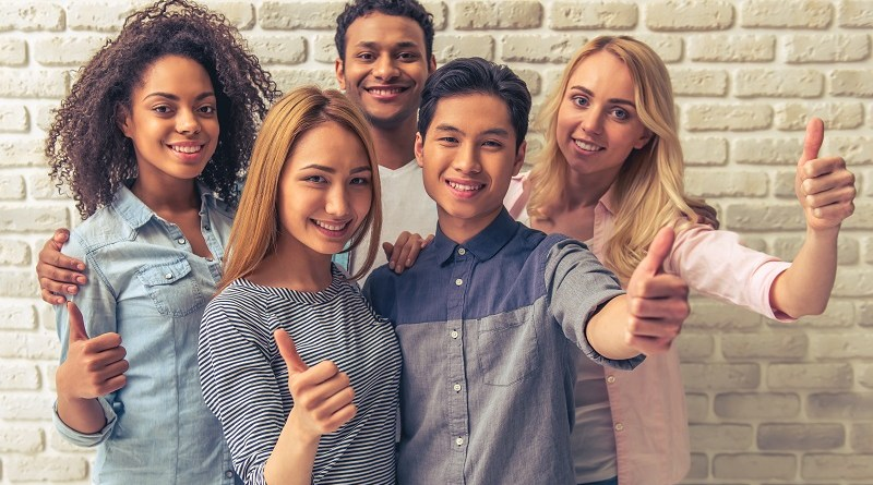 Portrait of beautiful young people of different nationalities showing Ok signs, looking at camera and smiling, against white brick wall