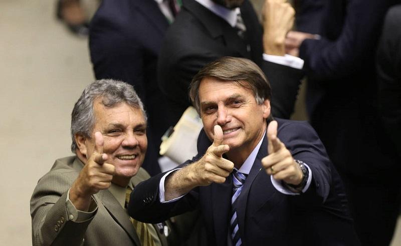 Em 2016, Alberto Fraga e Jair Bolsonaro fazem sinal com as mãos imitando armas de fogo durante a votação em segundo turno do projeto que muda a maioridade penal - Alan Marques - 19.ago.2015/Folhapress