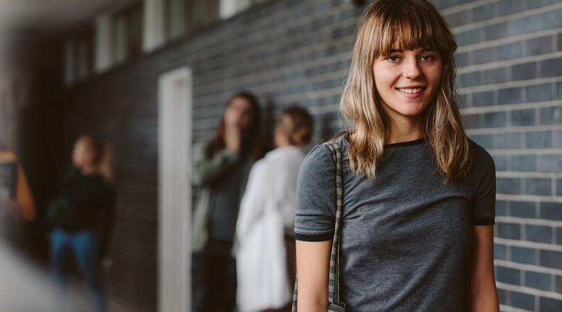 Portrait of beautiful young woman walking in college corridor with students standing in background. Female student in university campus.