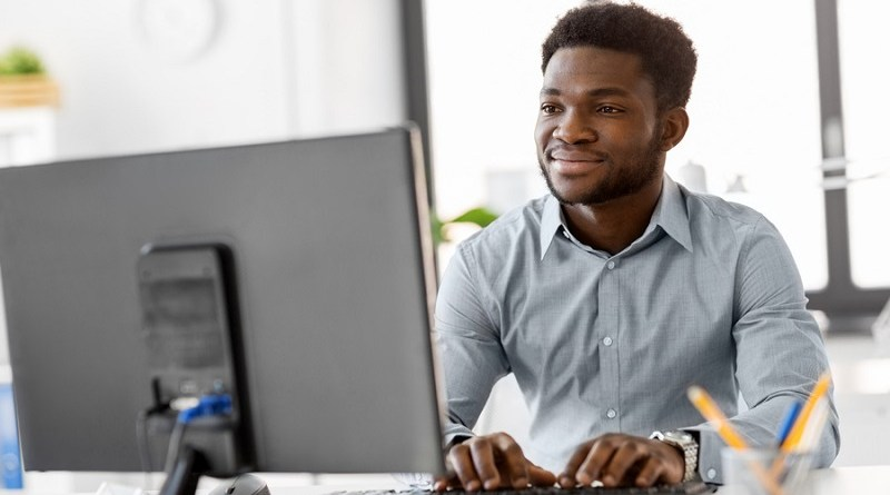business, people and technology concept - african american businessman with computer working at office