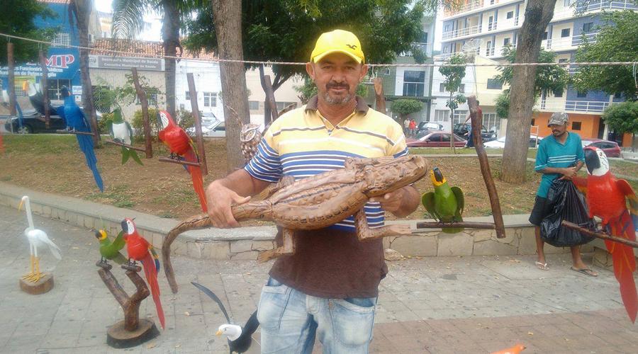 Homem vende artesanato feito de madeira, coco e pneus, em praça de Patos