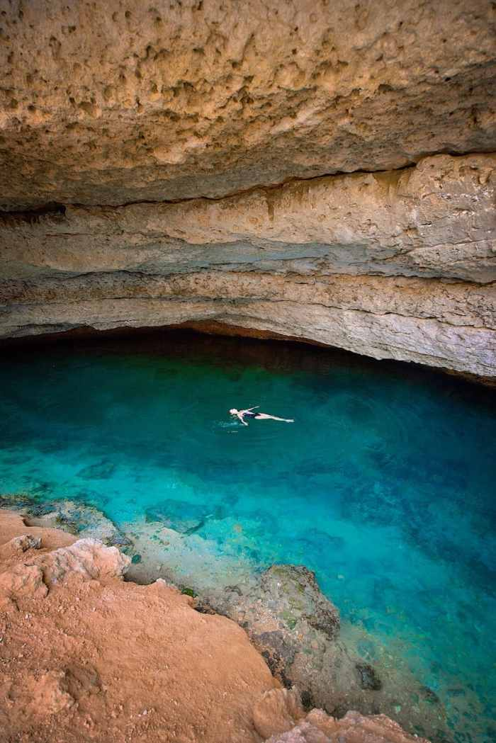 Swimming in the hidden cave area of Bimmah Sinkhole  in Oman