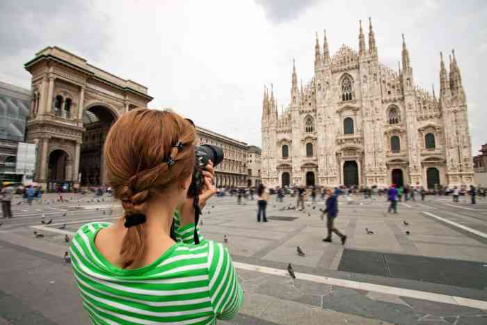 woman taking photos with extra memory cards on her Italy packing list