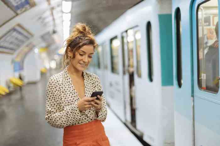woman on phone using app to get to Paris metro stations