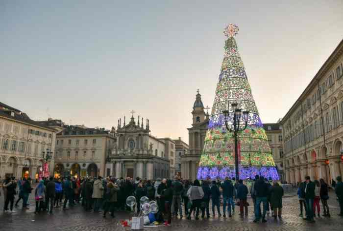 Turistas y lugareños se reúnen bajo un árbol de Navidad iluminado en Turín, Italia