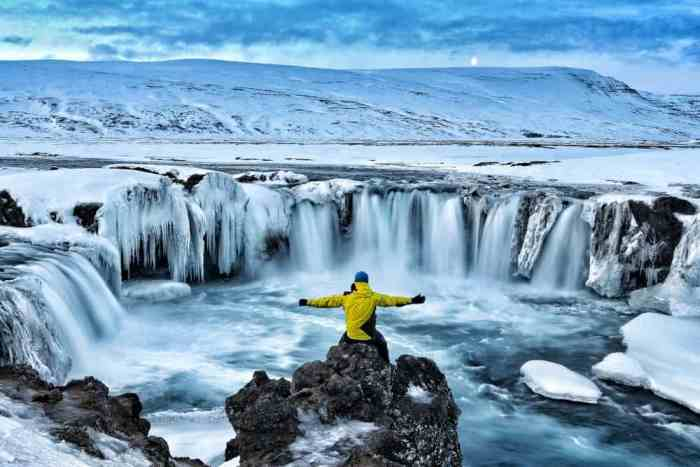 person sitting in snow at Godafoss during iceland in November