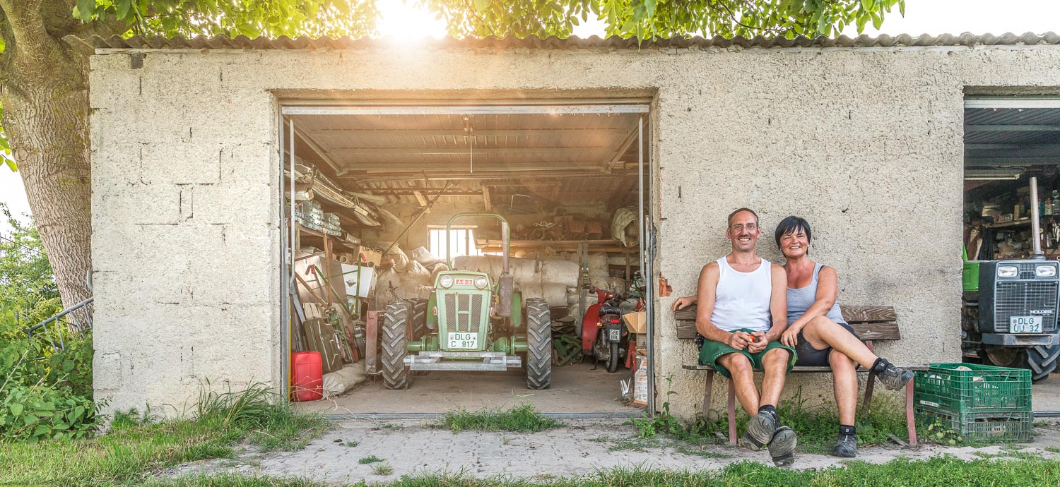 Martina and Manfred sitting in front of their market garden's garage on the bench