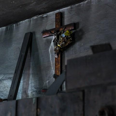 Das Kreuz Jesu, mit schwarzem Ruß überzogen, an der Wand.