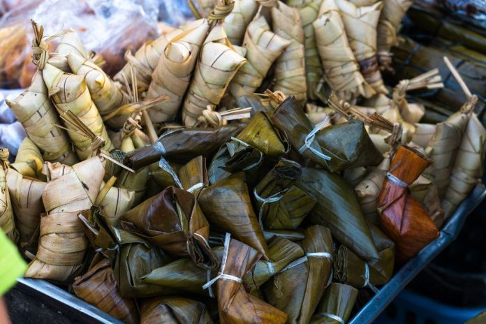 Banana Leaves.A picture containing food, pile, person, full