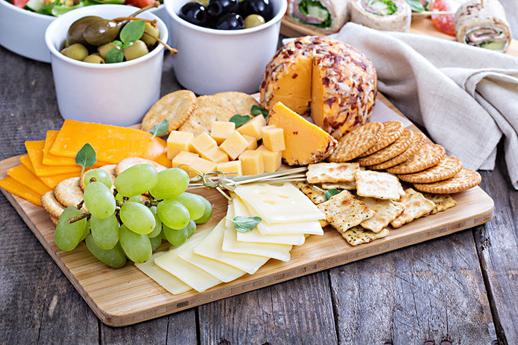 Azeitonas, uvas verdes, queijos esquisitos lindamente dispostos sobre a mesa, perda de peso dos biscoitos