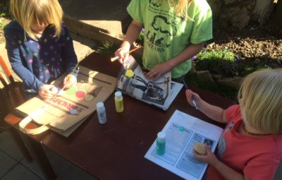 Kids decorating painting wooden Easter Eggs
