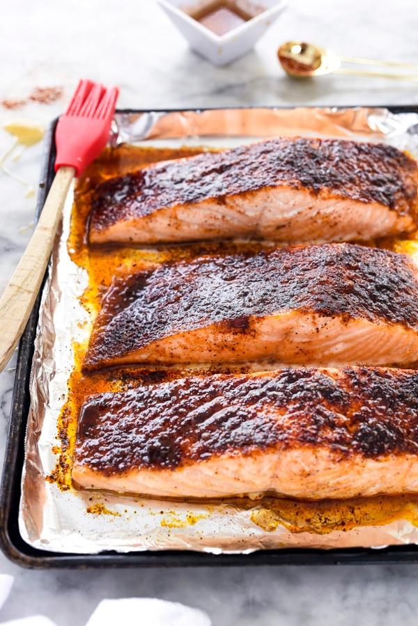 three maple glazed salmon fillets on baking sheet