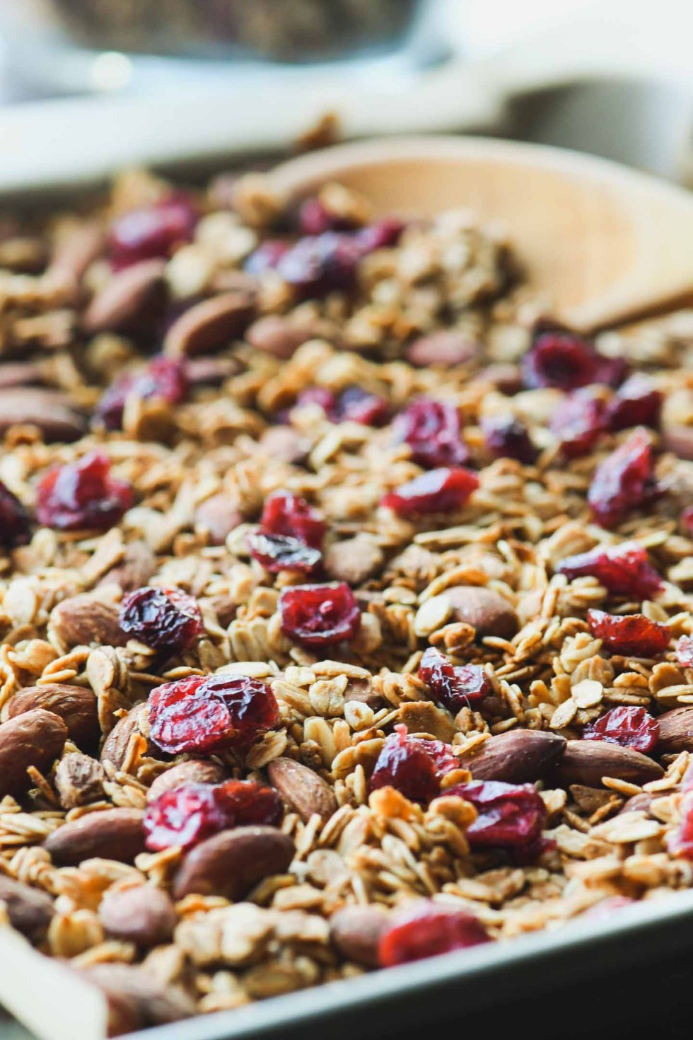 Homemade Honey Flax Granola sprinkled with dried cranberries on a baking sheet