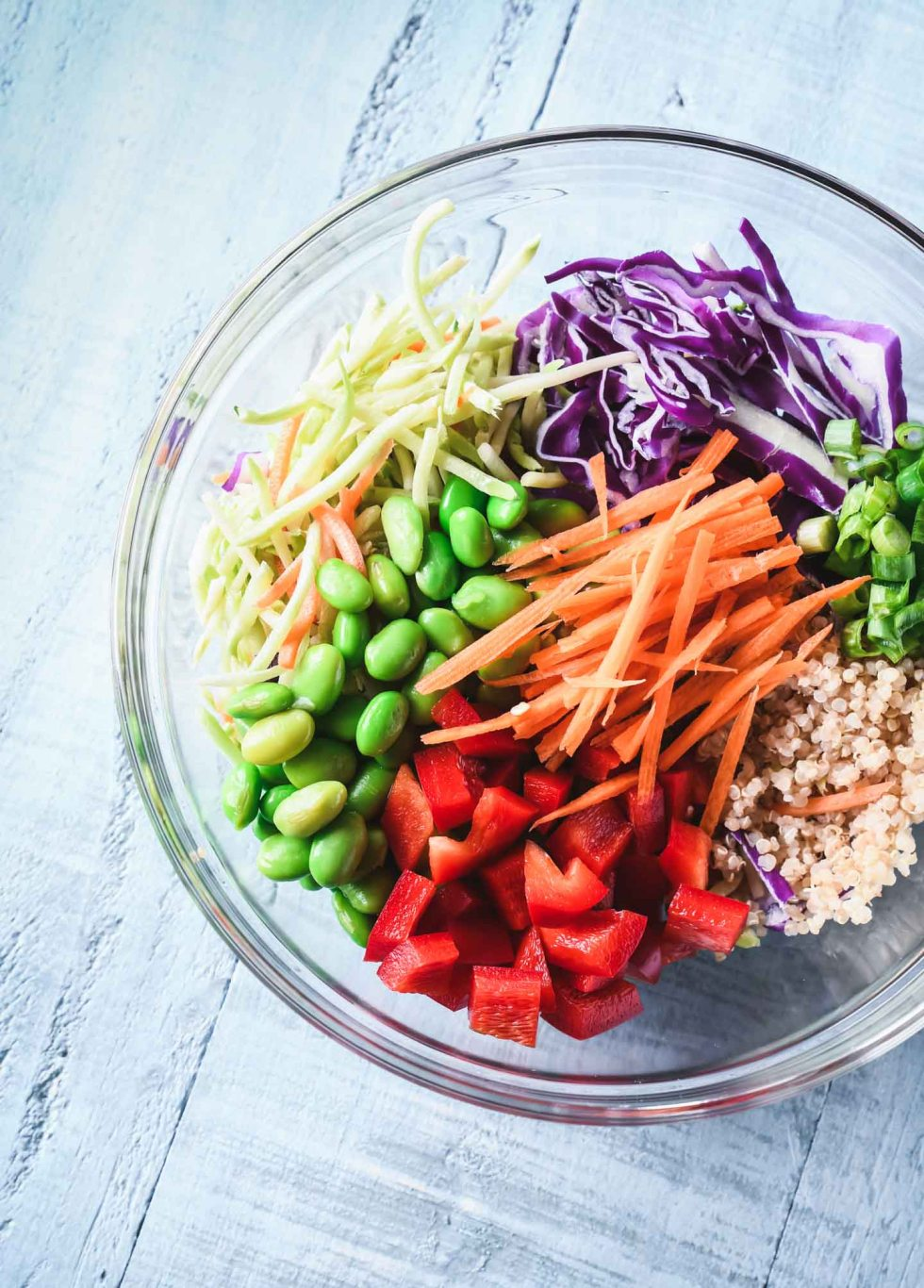 Ingredients for Asian quinoa salad - edamame, broccoli slaw, carrots and red cabbage in a clear bowl