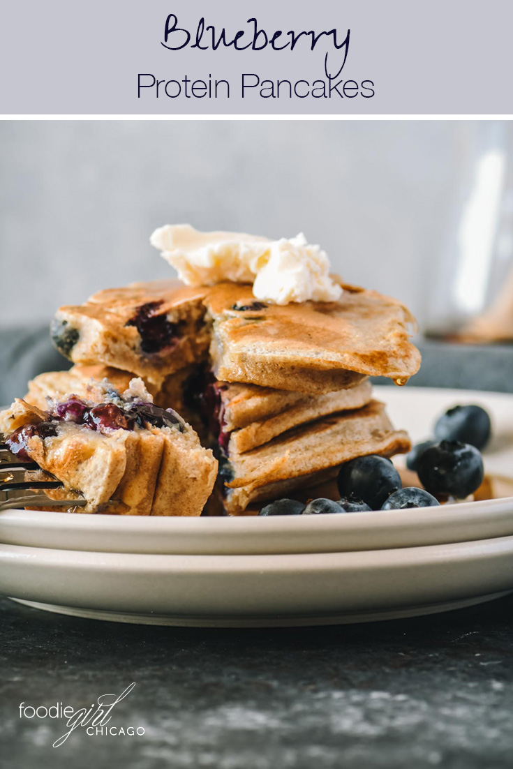 A stack of blueberry protein pancakes with a bite on a fork.