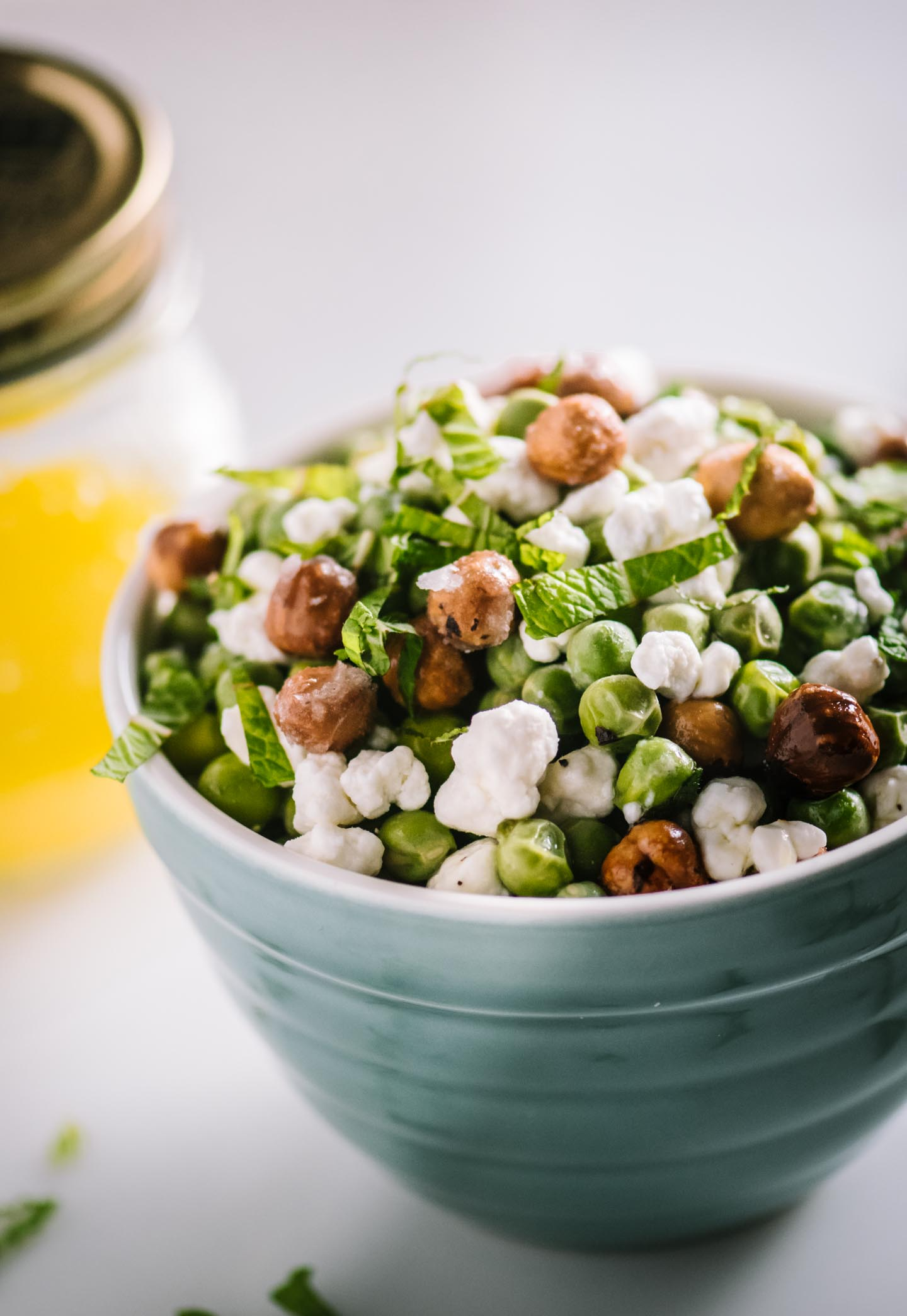 Fresh English Pea salad with candied hazelnuts and goat cheese in a small teal bowl