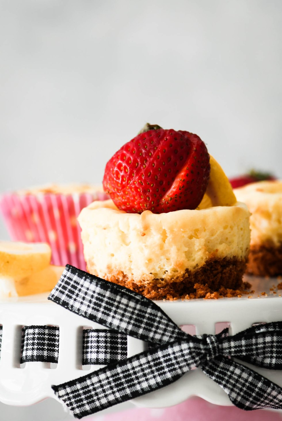 Individual min lemon cheesecake topped with a sliced strawberry