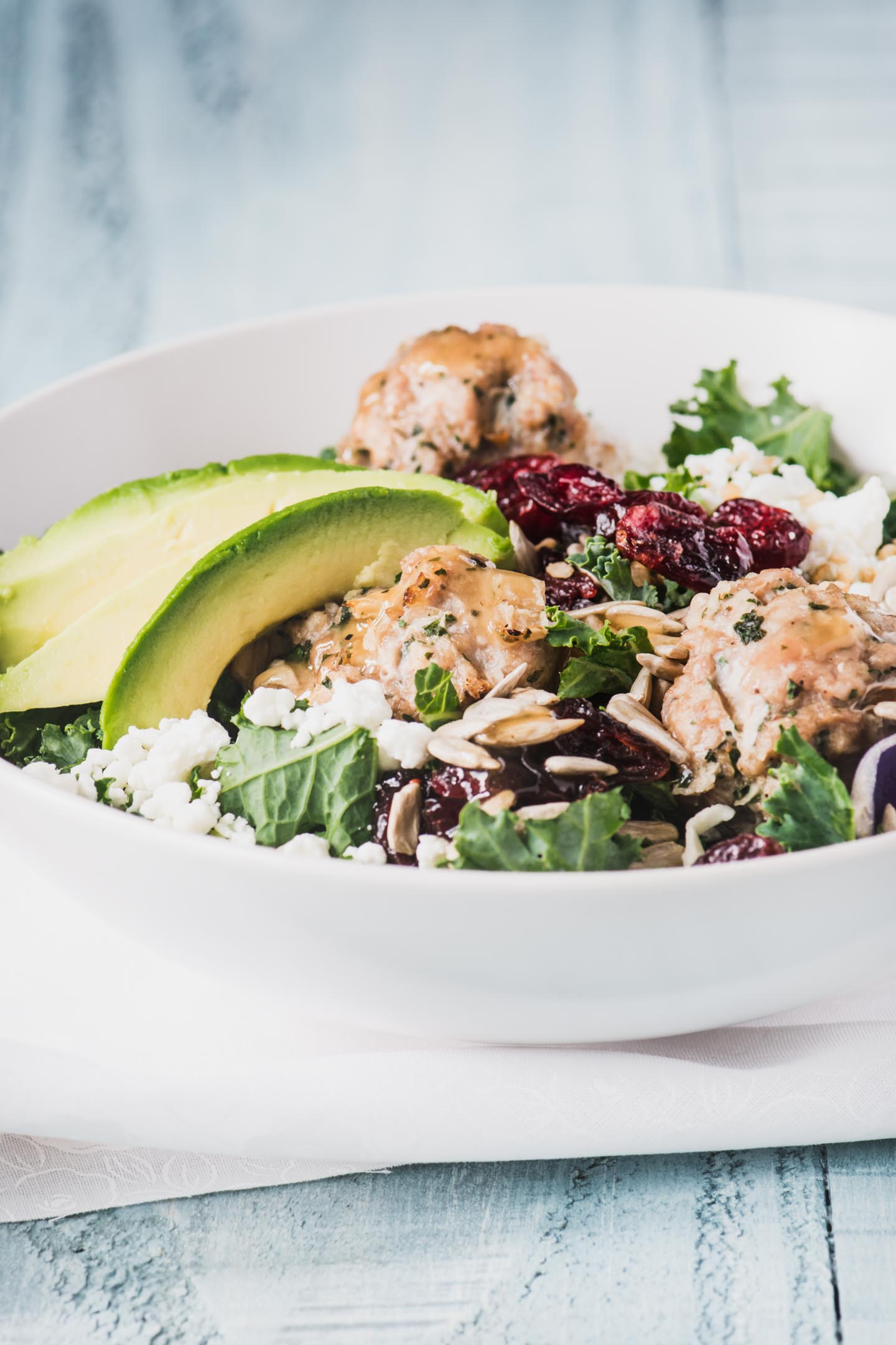 Close-up of kale salad greens topped with turkey meatballs and avocado