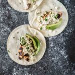 Three grilled chicken tacos topped with elotes and avocados