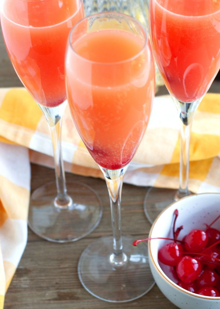 3 glasses of mimosas with a bowl of cherries