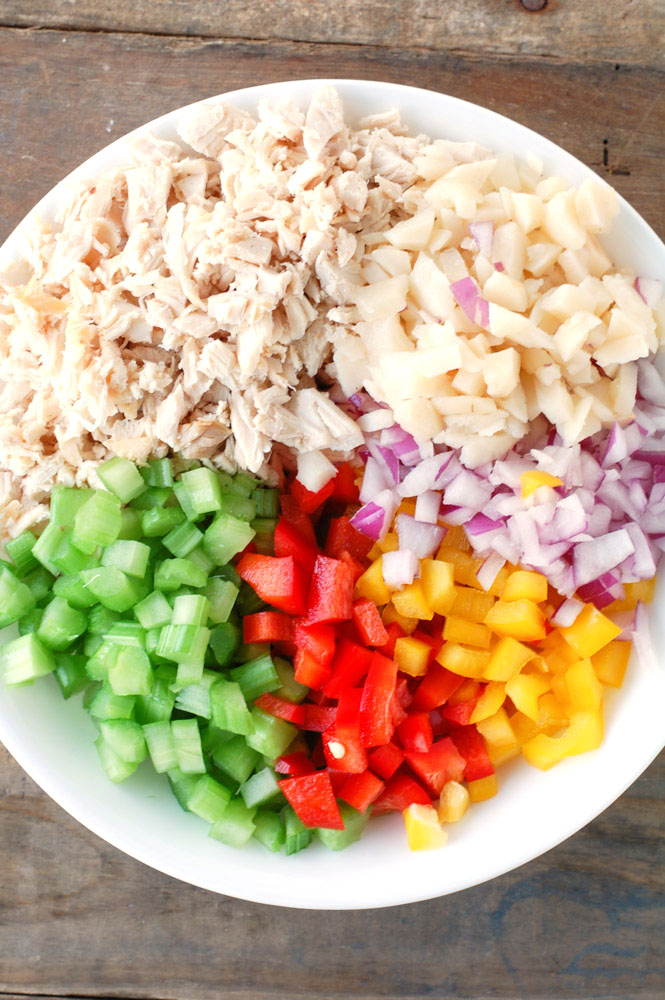 Shredded chicken, water chestnuts, red onion, bell peppers and celery in a bowl