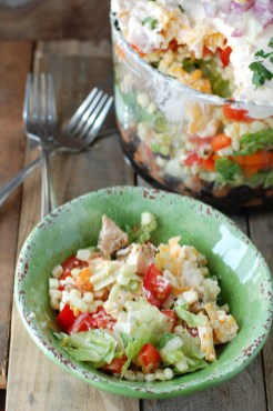 Green bowl with salad and forks off to the side.