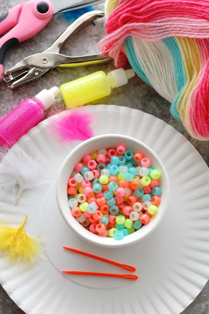 Bowl of beads, glitter glue and yarn