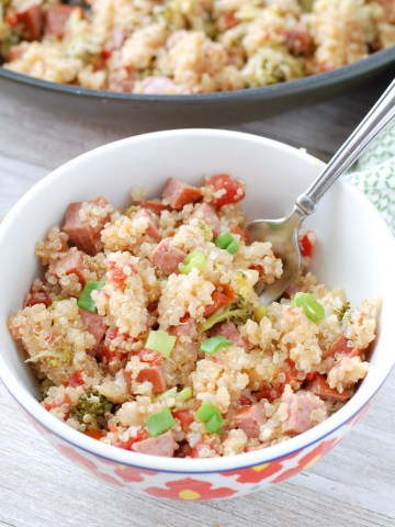 Bowl of quinoa, sausage and onions with a fork.