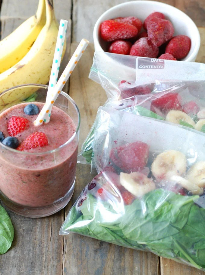 Glass of smoothie with bags of frozen spinach, banana, strawberry and blueberries