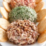 Pecan and chive cheese ball on plate with crackers.