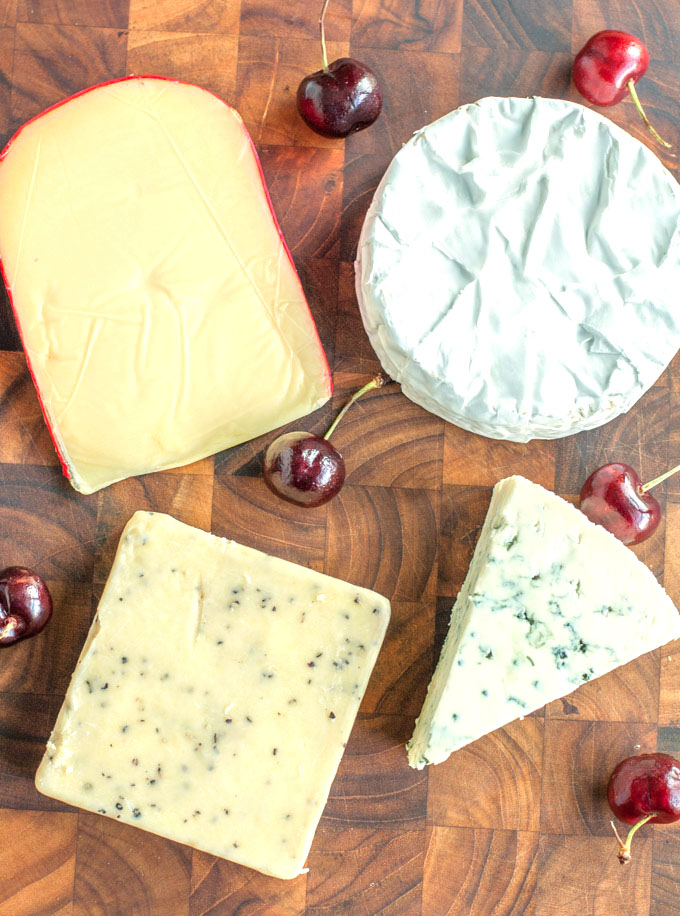 Four different cheeses on a cutting board with cherries