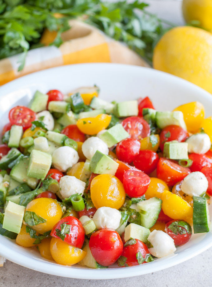 Cucumber Tomato Avocado Salad, a colorful and delicious salad filled with tomatoes, cucumbers, mozzarella cheese, avocado, herbs and lemon dressing.