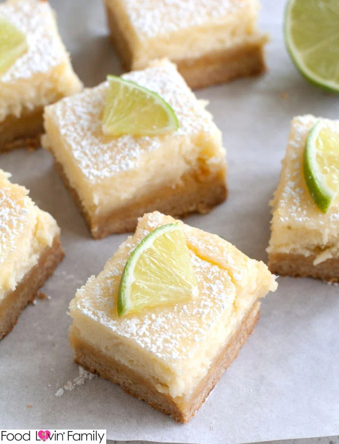 Margarita Bars are a delicious take on ooey gooey butter cake bars. They are cut into squares on parchment paper topped with lime wedge.