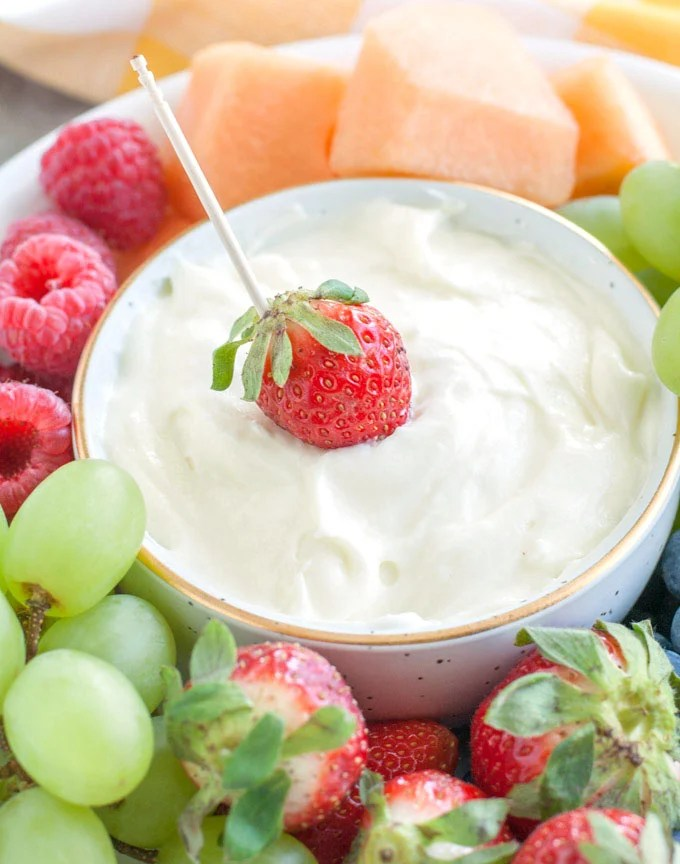 Cream cheese fruit dip in a bowl with a strawberry and toothpick