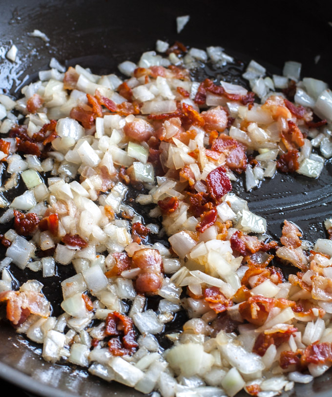 diced bacon and onion cooking in a skillet